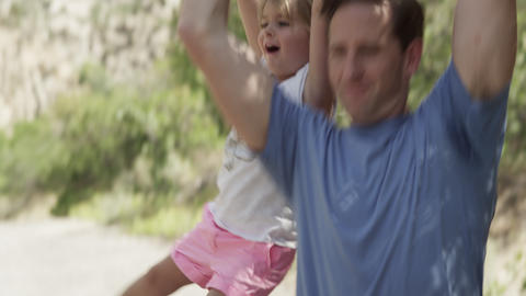 Dad picks up daughter and swings her over his back Footage