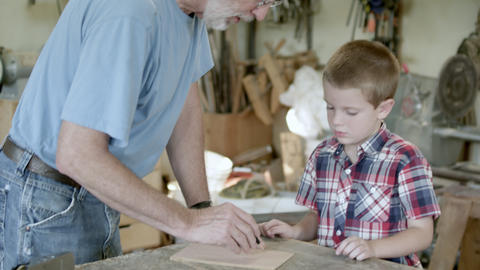 Grandfather drawing lines on a piece of wood, while grandson watches Footage