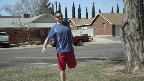 Man finishing jogging in suburban area checks time and starting to stretch Footage