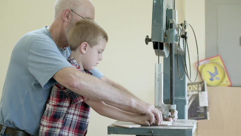 Grandfather helping and guiding grandson cut wood with an band saw Footage