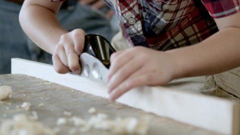 Grandfather watching a young boy how to use a wood plane.... Stock Video Footage