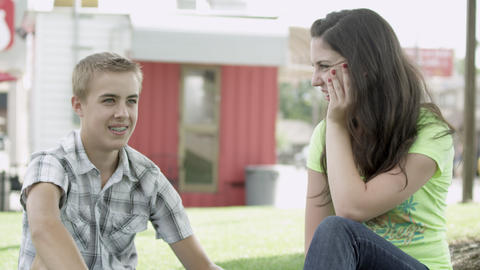 Teenage boy and girl holding hands while sitting on the grass Footage