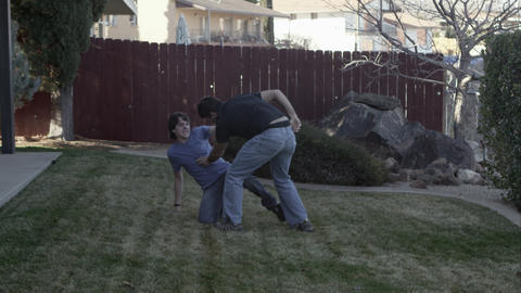Father and son wrestling iin the back yard as dad injures his lower back Live Action