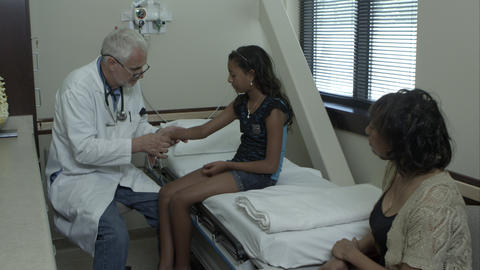 Doctor examines the wrist of a young girl. With mother in room Footage