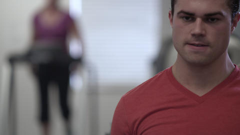 Man rolling shoulders with an out of focus woman on a treadmill behind Footage