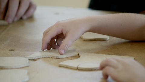 Young girl and boy in wood shop with older man playing with wood puzzle pieces Footage