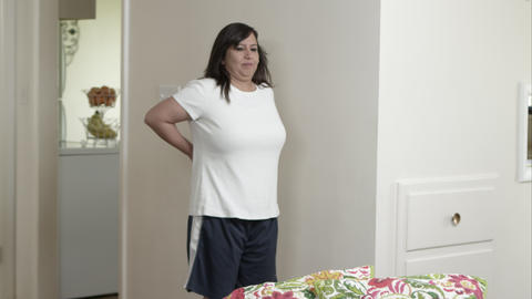 Woman stops in home with back pain Live Action