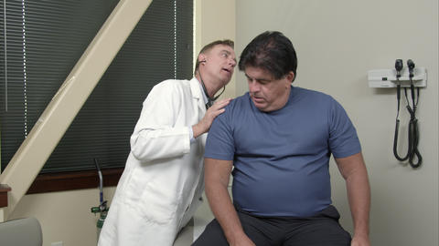 Doctor examining man's ears, and breathing Footage