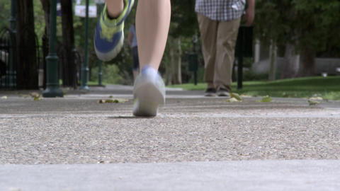 Low angle shot of a a woman jogging toward the camera. Others walk in background Footage