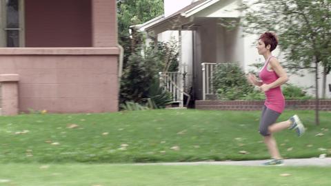 Trucking shot from street as woman runs down sidewalk Footage