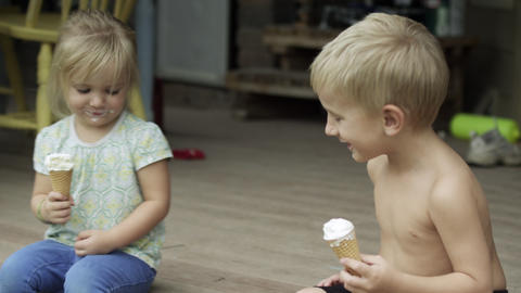 Young boy and girl on the porch with icecream cones, scooting toward and way fro Footage
