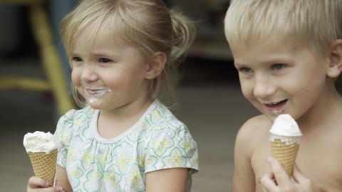 Young boy and girl on the porch with icecream cones, smiling Footage