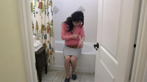 Woman in bathroom tweezing something on her arm Footage