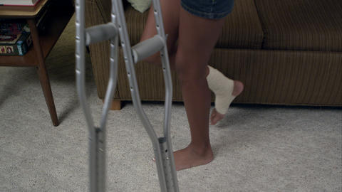 Young girl moving to couch to on crutches. She starts reading Footage