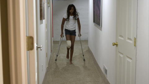 Young girl going down hallway on crutches Footage