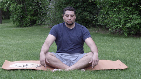 Man on yoga man in grass rotating neck and arm joints Footage
