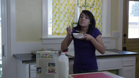 Woman in kitchen pouring milk on her bowl of cerel Footage