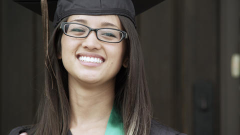 Young woman, in a graduation cap and gown, adjusting her hair Footage