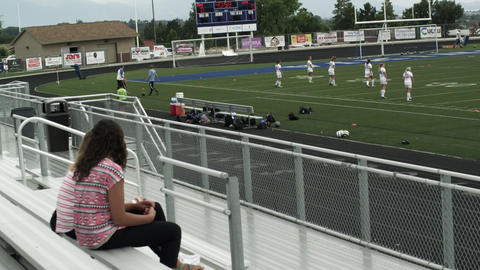 Two teenage girls watching girls' soccer practice from the bleachers Footage