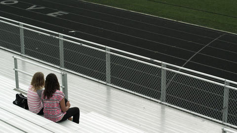Two teenage girls watching the field from the bleachers Footage