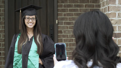 Mother taking a picture of her daughter in cap and gown Footage