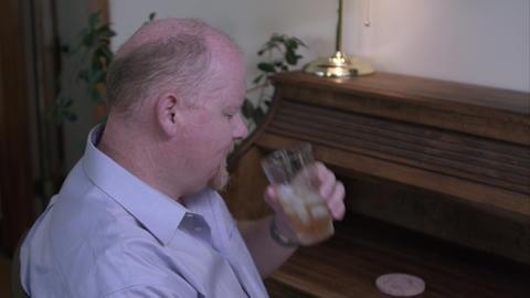 Man at a desk drinking liquor Footage
