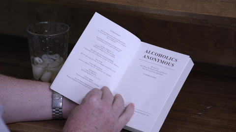 Man reading the an Alcoholics' Anonymous book. Glass of liquor on desk Footage