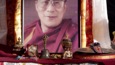 Tilting shot up from a sand mandala to a portrait of the Dalai Lama Footage