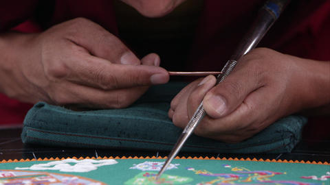 Tight shot of a man carefully adding sand to a colorful sand mandala, tilts up t Footage