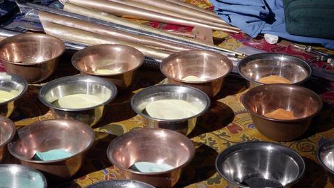 Tilting down shot of bowls of colored sand for making sand mandalas Live Action