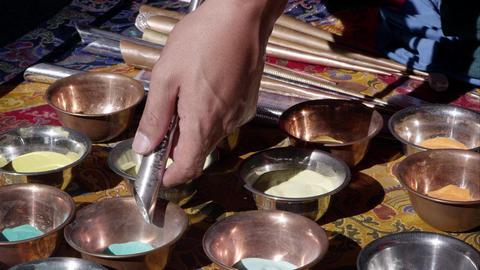 Mand returning colored sand to a bowl. Sand mandala Footage