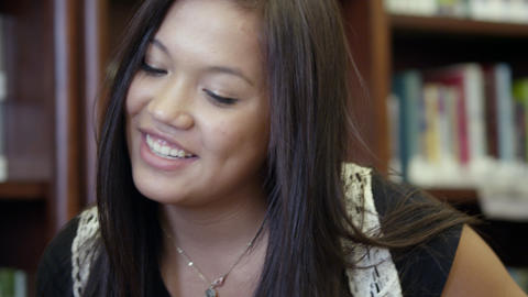 Teenage girl sits next to friend in library Footage