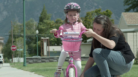 Mother helping daughter to learn to ride a bike Footage