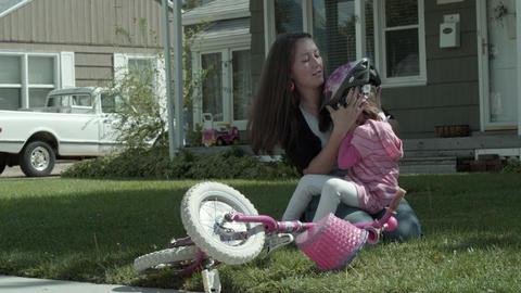 Mother conforting daughter after bike crash Footage