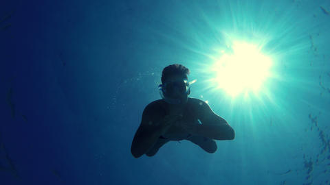 Young man swims towards the camera, grabs it and makes the cut Footage