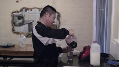 Man pouring fruit smoothy into a glass to drink it Footage