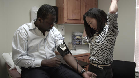 Doctor taking a blood pressure reading of a man Live Action