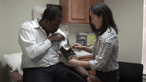 Doctor taking a blood pressure reading of an adult man Live Action