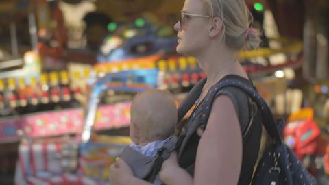 Mum with baby walking at funfair GIF