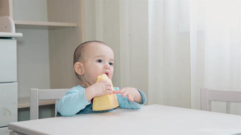 A hungry child is sitting at a white Desk in the children's home and eating home Live Action