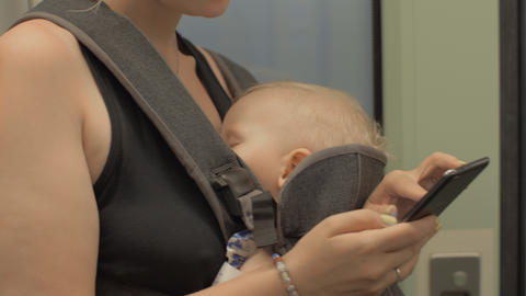 Woman with baby using mobile when traveling by underground train GIF