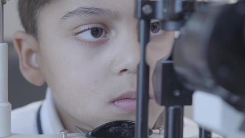 African american little boy doing eye test with optometrist looking at eye test Footage