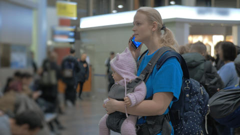 Mother with baby daughter waiting at the airport, woman talking on mobile Footage
