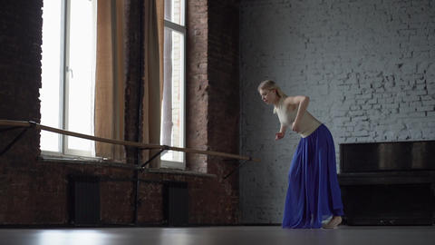 Amazing blonde dancer makes twine one one leg in blue skirt Footage