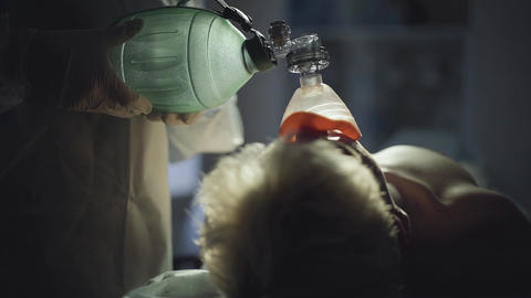 Doctors hands in white coat pumping oxygen mask for a man. Close up Live Action