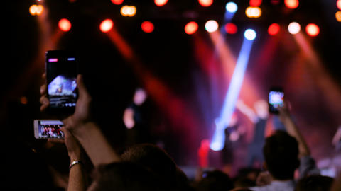People hands silhouette recording video of live music concert with smartphone ライブ動画