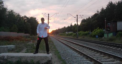 Gentalman juggler at sunset makes tricks on the railway Footage