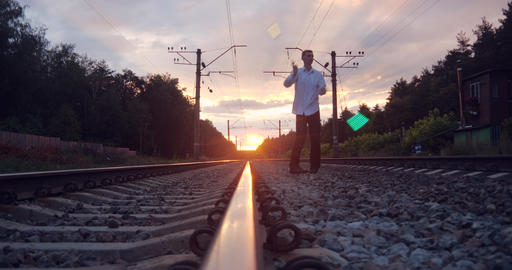 4k - gentalman artist makes trick on the railway at sunset Live Action