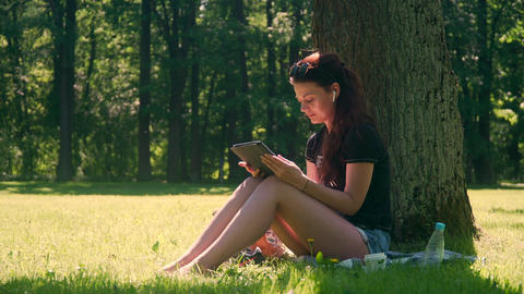 Young woman in park uses smartphone and tablet Footage