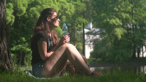 Young woman drinking water from bottle in park Footage